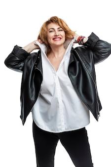 Gelukkige vrouw op middelbare leeftijd met rood haar in een leerjasje