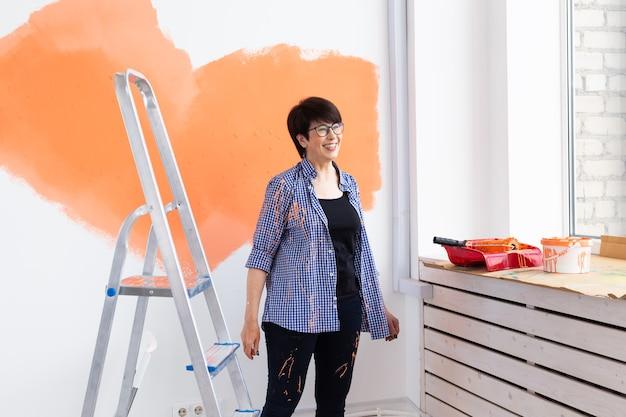 Gelukkige vrouw op middelbare leeftijd schilderen muur in haar nieuwe appartement. renovatie, herinrichting en reparatie