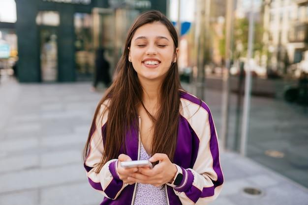 Gelukkige vrouw op straat die een smartphone gebruikt en naar de camera kijkt