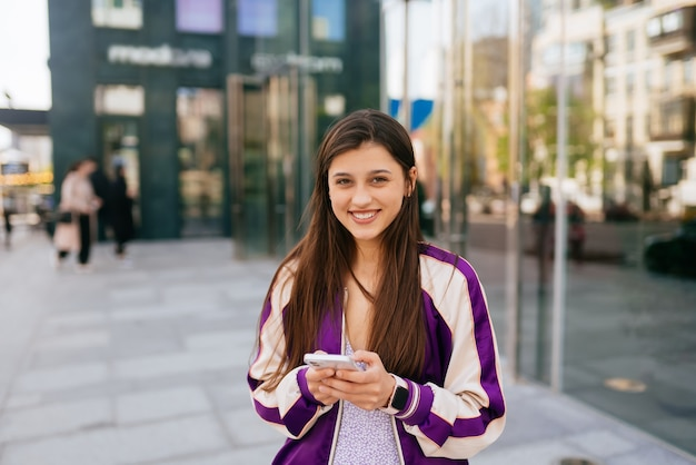 Gelukkige vrouw op straat die een smartphone gebruikt en naar de voorkant kijkt