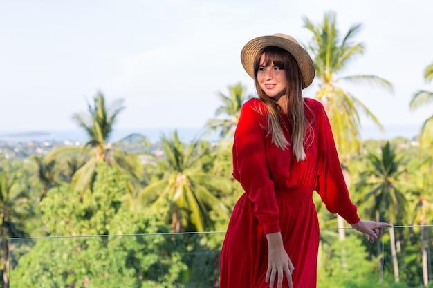 Gelukkige vrouw op vakantie in rode zomerjurk en strohoed op balkon met tropisch uitzicht op zee en palmbomen.