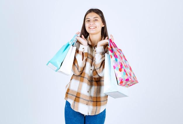 Gelukkige vrouw op zoek naar stelletje boodschappentassen over witte muur.