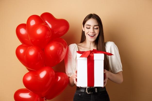 Gelukkige vrouw open valentijnsdag geschenk, glimlachend opgewonden en kijken naar huidige doos