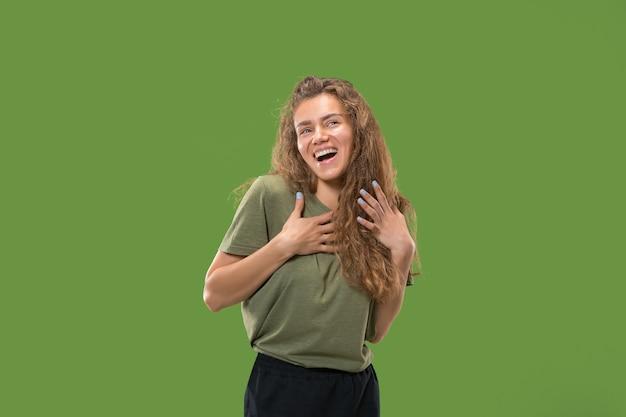Gelukkige vrouw permanent en glimlachend geïsoleerd op groen