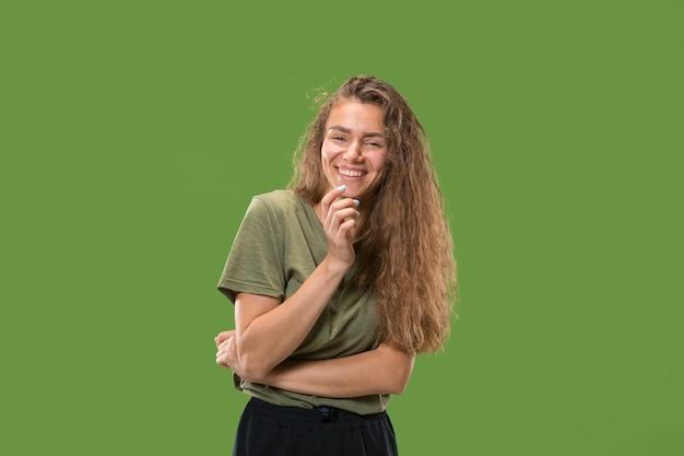 Gelukkige vrouw permanent en glimlachend geïsoleerd op groene studio achtergrond. mooi vrouwelijk portret van halve lengte. jonge emotionele vrouw.