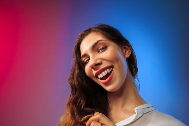 Gelukkige vrouw permanent en glimlachend op gekleurde muur