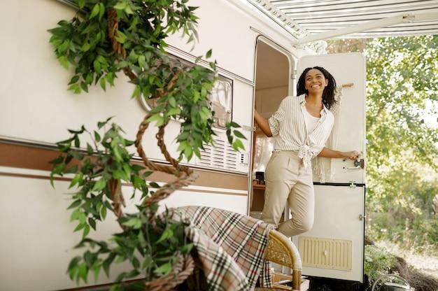 Gelukkige vrouw poseert bij de ingang van de camper, kamperen in een aanhangwagen. stel reist op busje, vakanties op camper