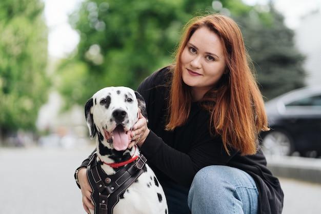 Gelukkige vrouw poseren en spelen met haar dalmatische hond tijdens een stadswandeling