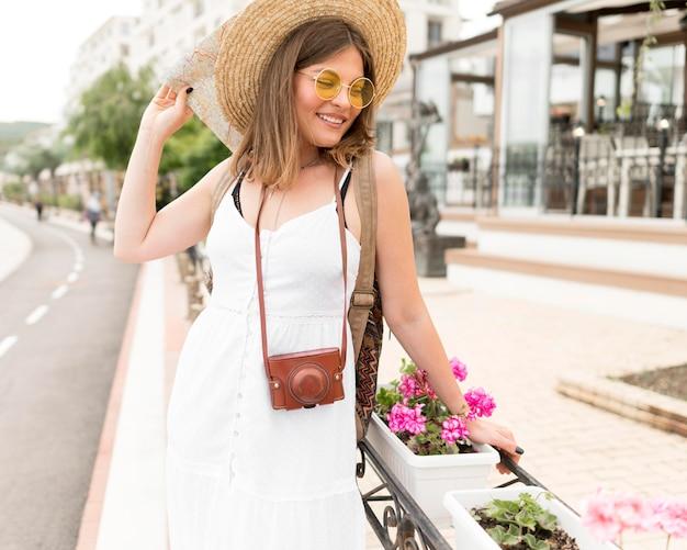 Gelukkige vrouw poseren in de buurt van bloemen