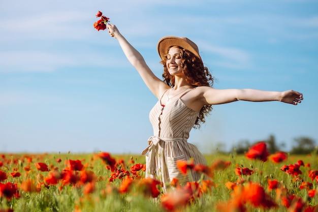Gelukkige vrouw poseren in een papaverveld a