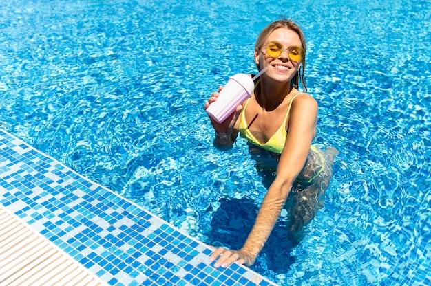 Gelukkige vrouw poseren in zwembad