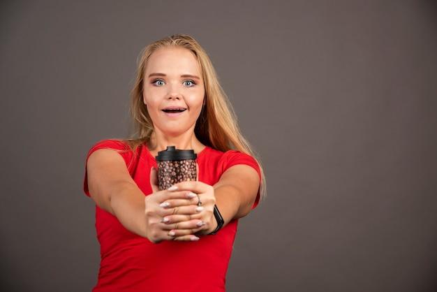 Gelukkige vrouw poseren met afhaalmaaltijden koffie op zwarte muur.