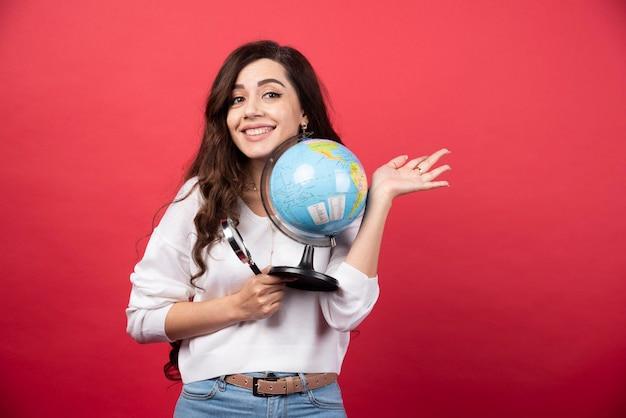 Gelukkige vrouw poseren met globe en vergrootglas. hoge kwaliteit foto