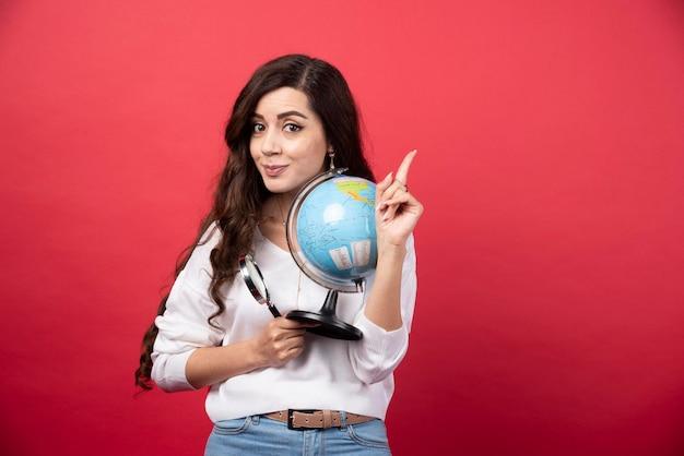 Gelukkige vrouw poseren met globe en vergrootglas terwijl ze naar boven wijst. hoge kwaliteit foto