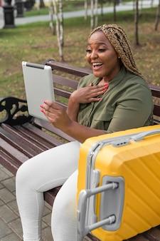 Gelukkige vrouw praten met een vriend op haar tablet