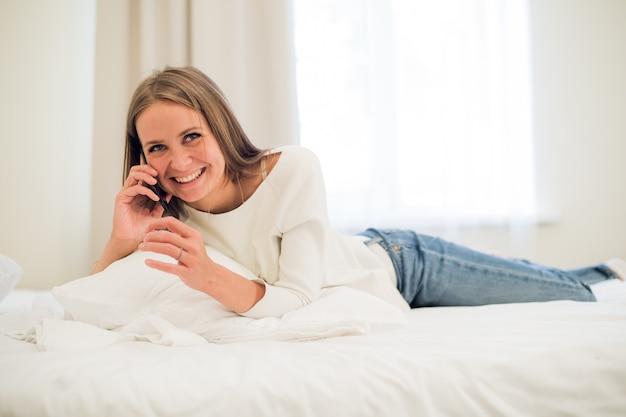 Gelukkige vrouw praten over een telefoon in bed