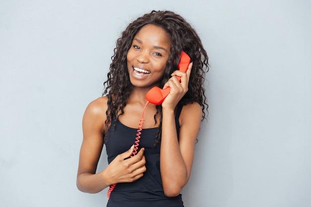 Gelukkige vrouw praten over retro telefoon buis over grijze muur
