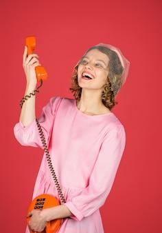 Gelukkige vrouw praten over retro telefoon mooie vrouw in roze jurk met telefoonhoorn gelukkige vrouw
