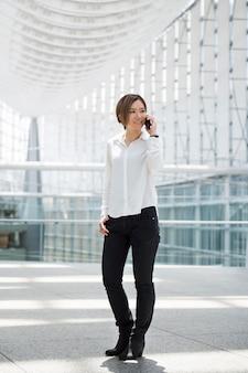 Gelukkige vrouw praten over telefoon volledig schot