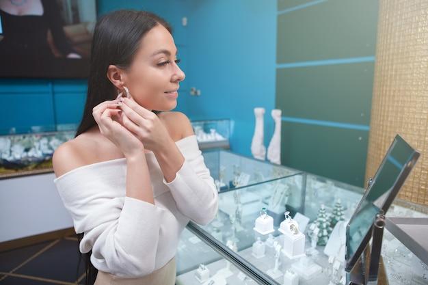 Gelukkige vrouw probeert op oorbellen voor de spiegel bij juwelier
