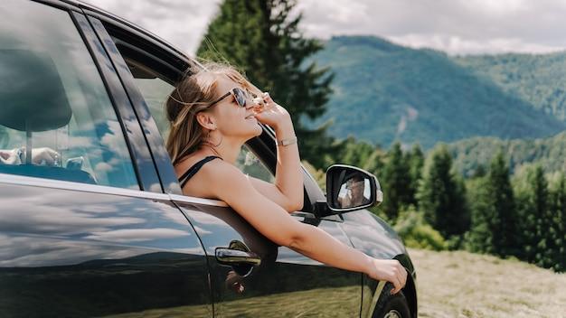 Gelukkige vrouw reist met de auto in de bergen. zomer vakantie concept. vrouw uit het raam genietend van uitzicht op de bergen