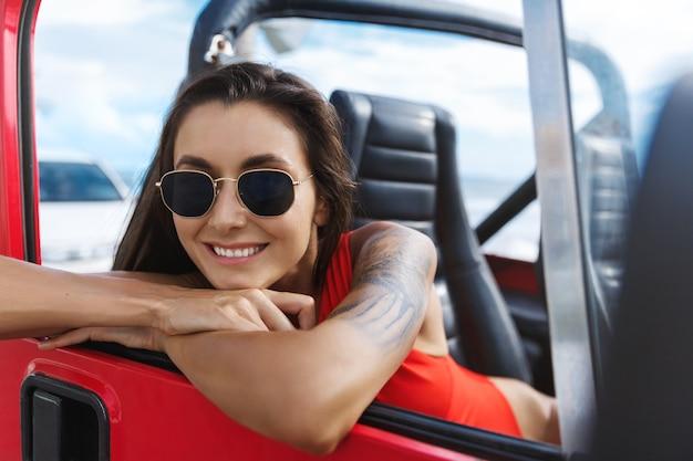 Gelukkige vrouw reizen naar het strand in suv-auto, zittend op passanger zitten in zwemkleding en zonnebril.