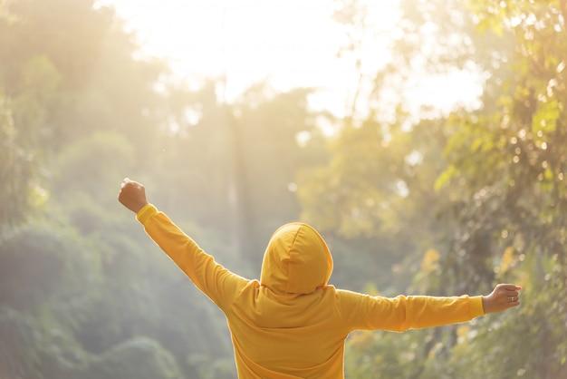 Gelukkige vrouw reiziger in gele trui met capuchon staat met opgeheven armen.