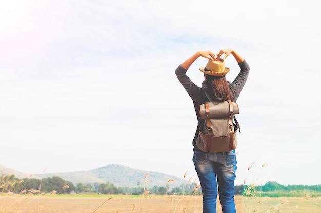 Gelukkige vrouw reiziger op zoek naar blauwe hemel en handen liefde teken, wanderlust reis concept, ruimte voor tekst