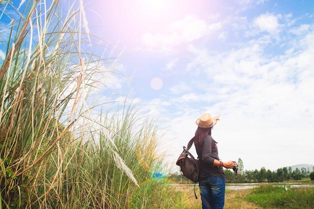 Gelukkige vrouw reiziger op zoek naar blauwe lucht met veld van gras, wanderlust reis concept, ruimte voor tekst