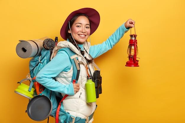 Gelukkige vrouw reiziger vormt met kleine lamp, klaar om onbekende plaats te verkennen, in hoge geest zijn, draagt grote rugzak op schouders, geïsoleerd op gele achtergrond