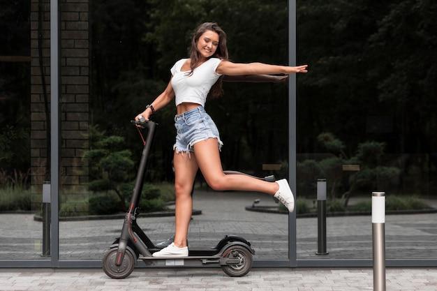 Gelukkige vrouw rijden elektrische scooter buitenshuis