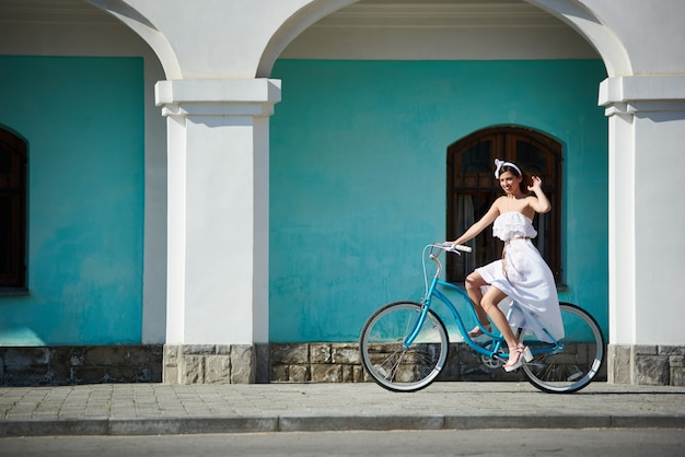 Gelukkige vrouw rijdt op een retro fiets in een hete zomerdag in de straten van de stad