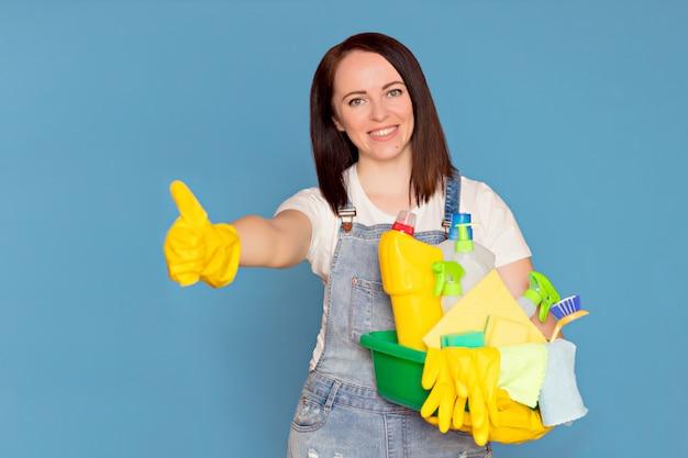 Gelukkige vrouw schoonmaakster met een emmer vol met kleurrijke wasmiddel in rubberen handschoenen,