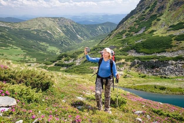 Gelukkige vrouw selfie maken in de bergen