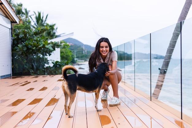 Gelukkige vrouw spelen met hond in terras met zeegezicht