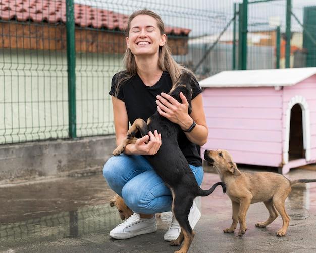Gelukkige vrouw spelen met reddingshonden bij adoptiecentrum