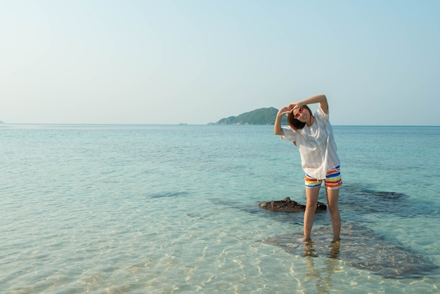Gelukkige vrouw staande armen gestrekt op het strand van sea