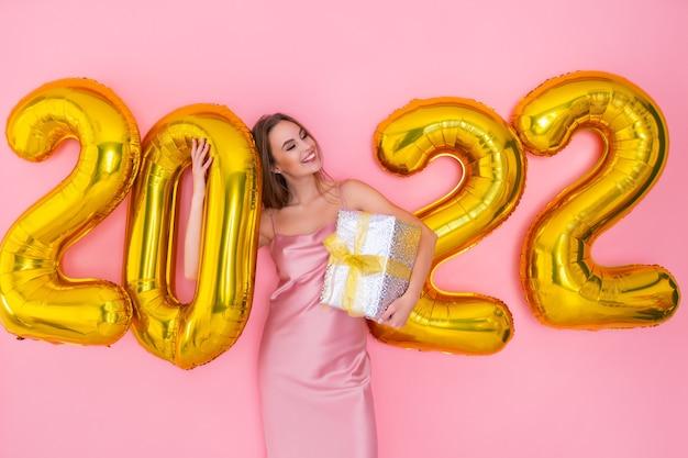 Gelukkige vrouw staat in de buurt van luchtballonnen houdt geschenkdoos op roze achtergrond nieuwjaarsviering