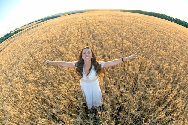 Gelukkige vrouw staat in de zomer in een tarweveld tegen de achtergrond van een ondergaande zon