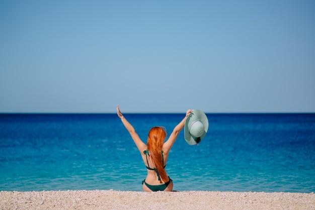Gelukkige vrouw steekt enthousiast haar handen omhoog zittend op het strand, zonnige dag