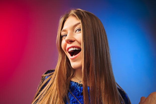 Gelukkige vrouw stond, glimlachend op gekleurde studio achtergrond. mooi vrouwelijk portret van halve lengte. jongeren stellen vrouw tevreden. menselijke emoties, gezichtsuitdrukking concept.