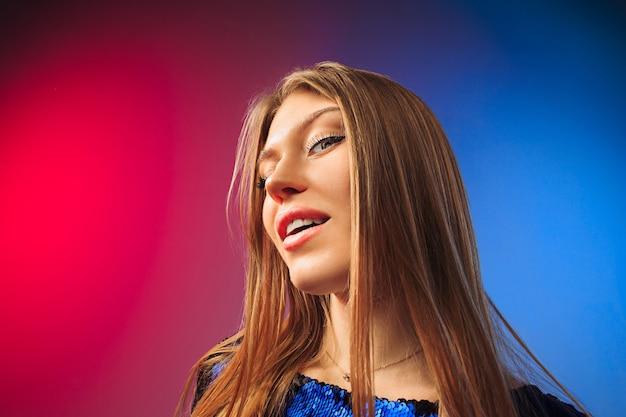 Gelukkige vrouw stond, glimlachend op gekleurde studio achtergrond. mooi vrouwelijk portret van halve lengte. jongeren stellen vrouw tevreden.