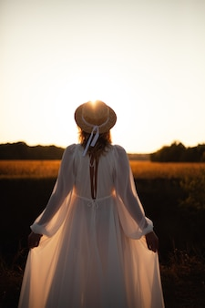 Gelukkige vrouw stond met haar rug op zonsondergang in de natuur.