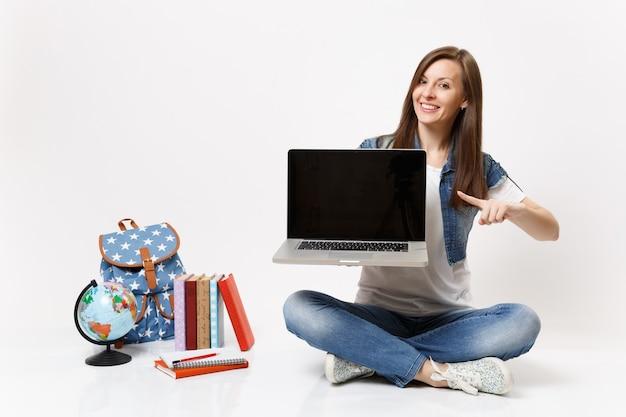 Gelukkige vrouw student wijzende vinger op laptop pc-computer met leeg zwart leeg scherm zitten in de buurt van globe, rugzak schoolboeken geïsoleerd