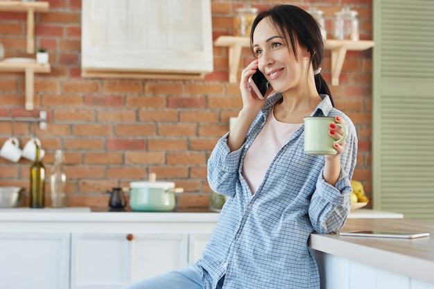Gelukkige vrouw terloops gekleed, chats met vriend via slimme telefoon, dranken drank staat in de keuken