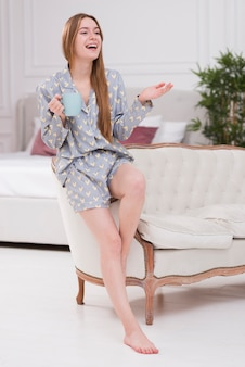 Gelukkige vrouw thuis met kop thee