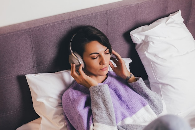 Gelukkige vrouw thuis op comfortabel bed, het dragen van warme kleren pullover, muziek luisteren