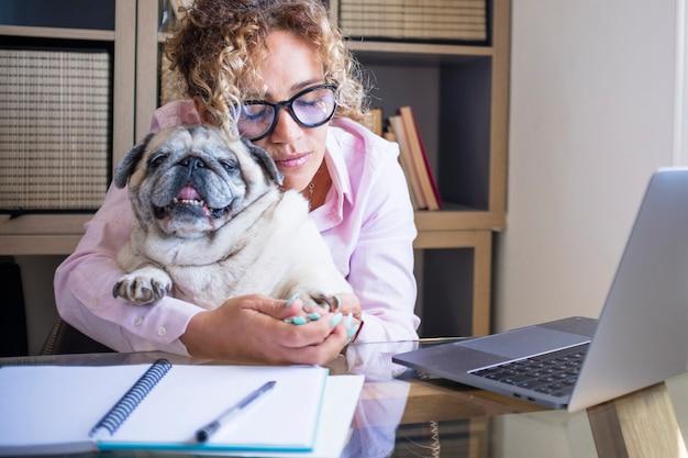 Gelukkige vrouw thuis verliefd op haar beste vriend pug dog terwijl ze werkt op de computer laptop op de desktop - slim werken en online baan vrouwelijke mensen met dier in liefde levensstijl