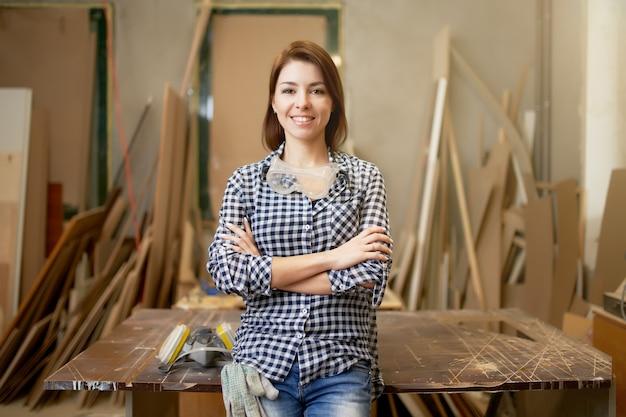 Gelukkige vrouw timmerman met gekruiste armen in workshop