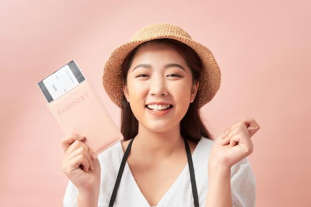 Gelukkige vrouw toont haar paspoort en camera geïsoleerd op roze